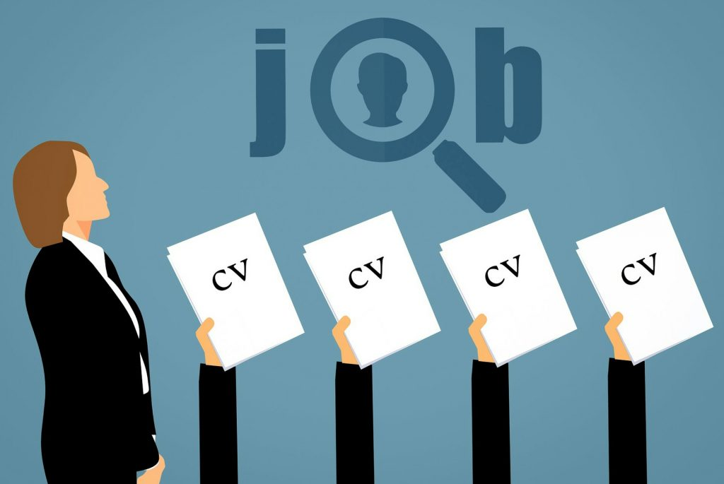 A clipart-style image describing a job hunt; one woman in a business suit stands on the left while four hands holding up CVs are arranged horizontally on her right. The word 'job' is stylized above the four hands.